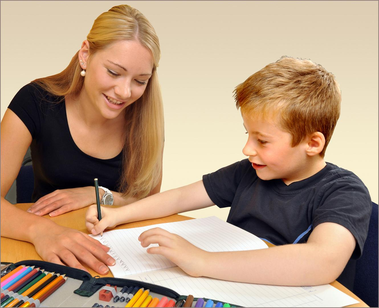 Tutor helping a boy with writing
